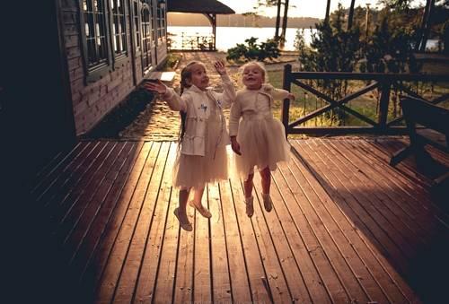 Dziewczynki skaczące na drewnianej podłodze